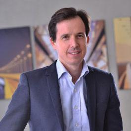 Un portrait de Julien Schloupt, souriant face caméra. Il porte une chemise bleu clair et un costume bleu foncé