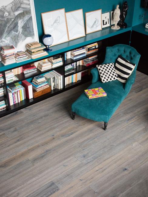 Parquet vieilli BerryAlloc dans une bibliothèque. Une méridienne en velours bleu roi invite à la lecture