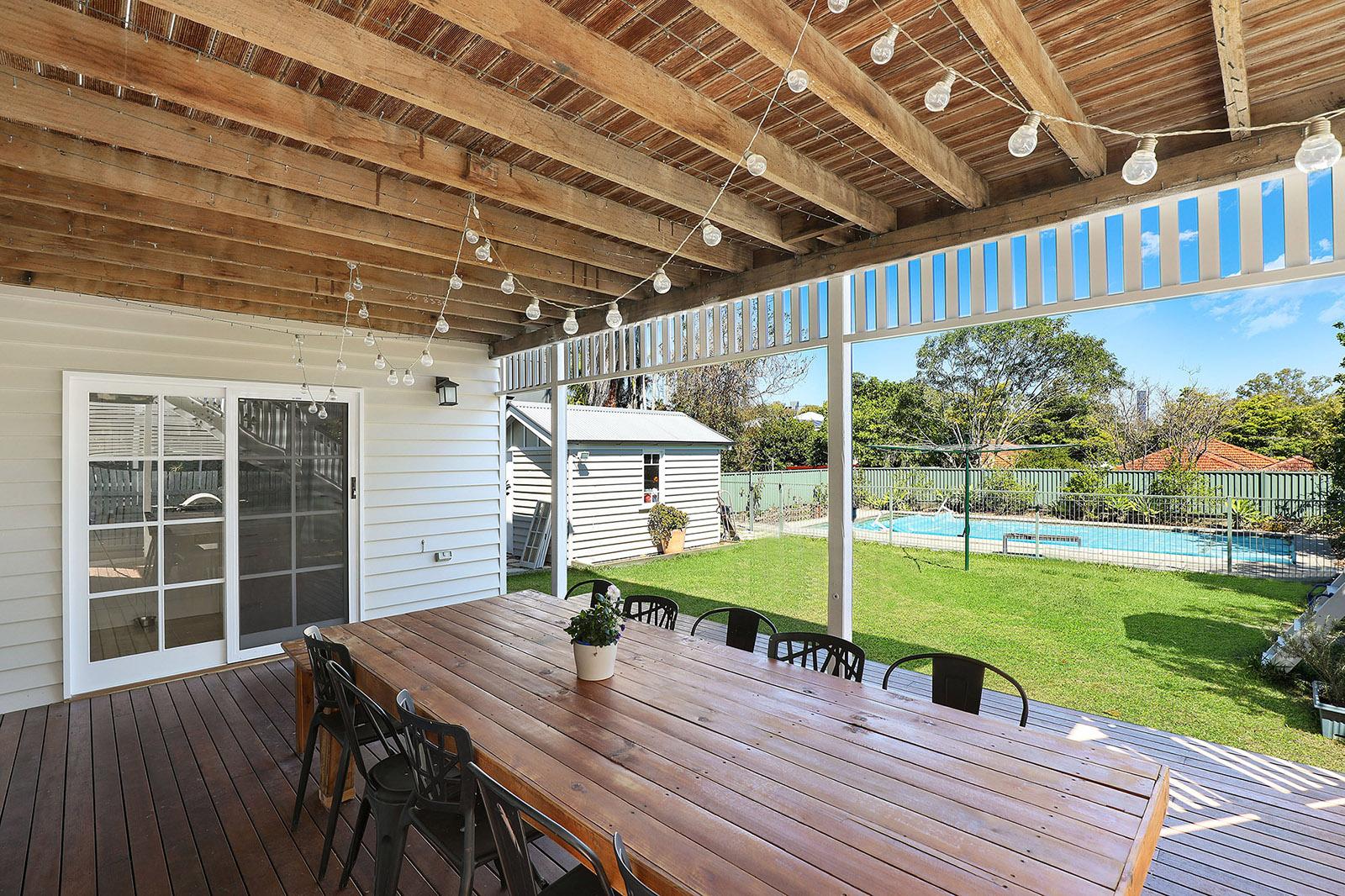 Une jolie terrasse en bois prend place sous un auvent. Une grande table rectanguaire en bois est entourée de chaises de jardin en métal. Au loin on voit une piscine entourée d'une pelouse verte.