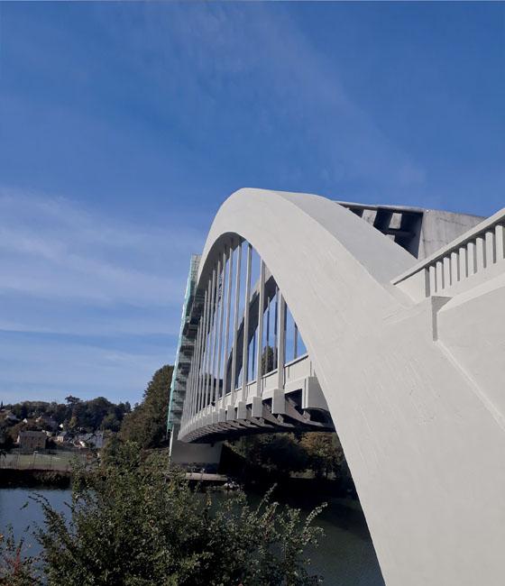 Un pont en béton de forme courbe enjambre une belle rivière
