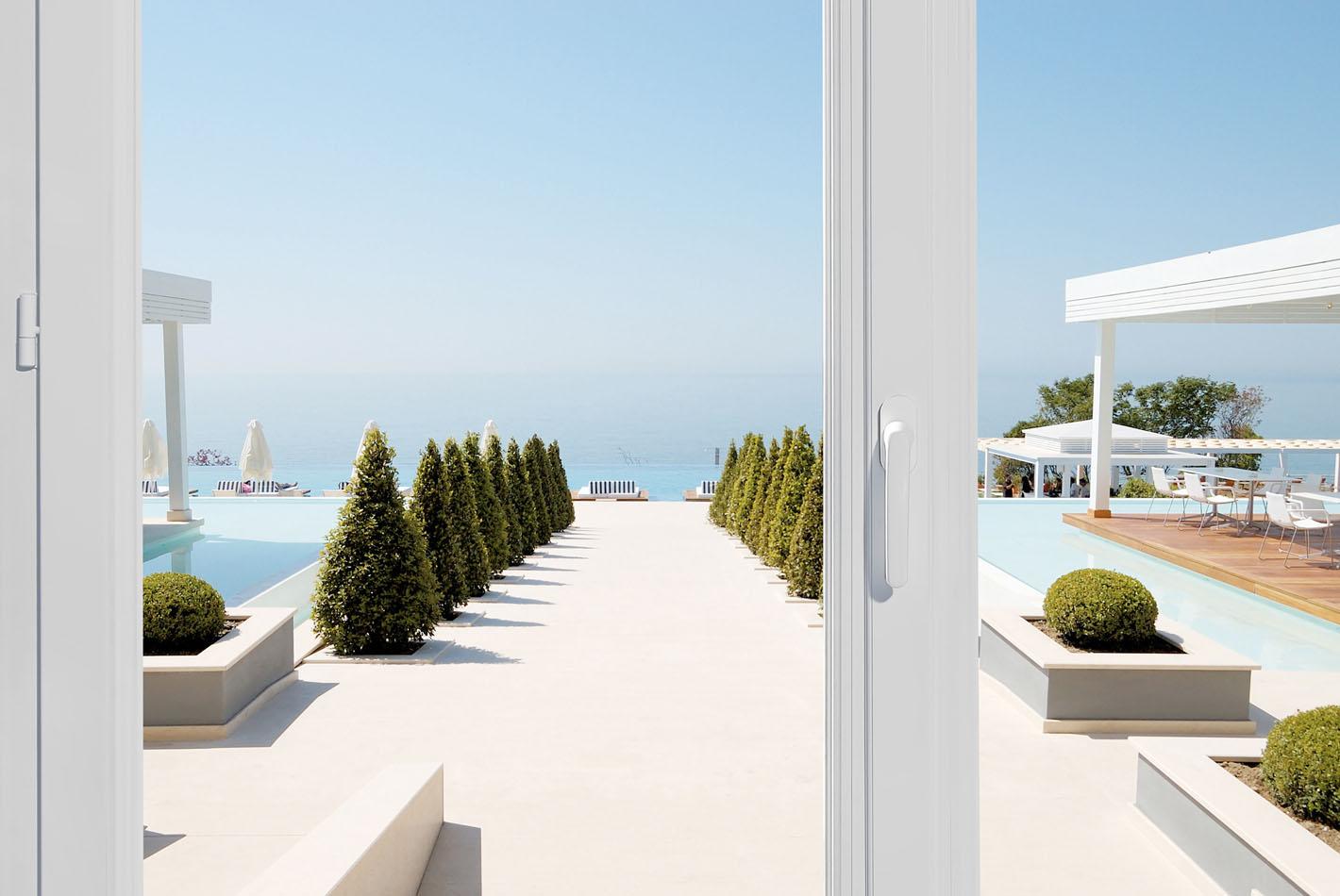 Une baie vitrée Prefal s'ouvre sur une magnifique terrasse ensoleillée. Au moin la mer bleue pour horizon.