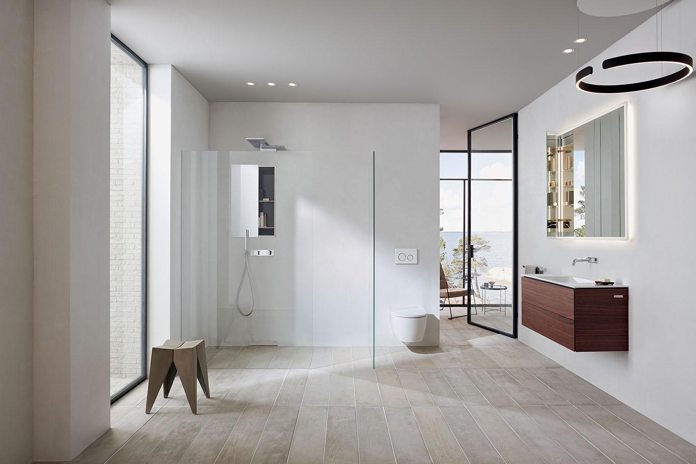 une salle de bain blanche et bois naturel, très épurée avec une vue sur la montagne. Collection Geberit One