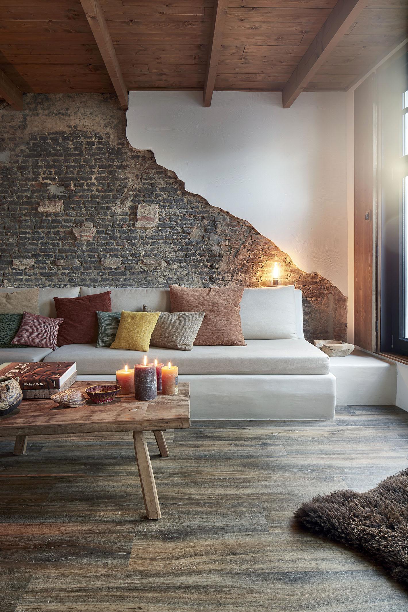 magnifique salon avec un canapé blanc, un mur en briques et un sol vinyle BerryAlloc. L'ambiance est réchauffée par de nombreuses bougies posées sur une table basse en bois